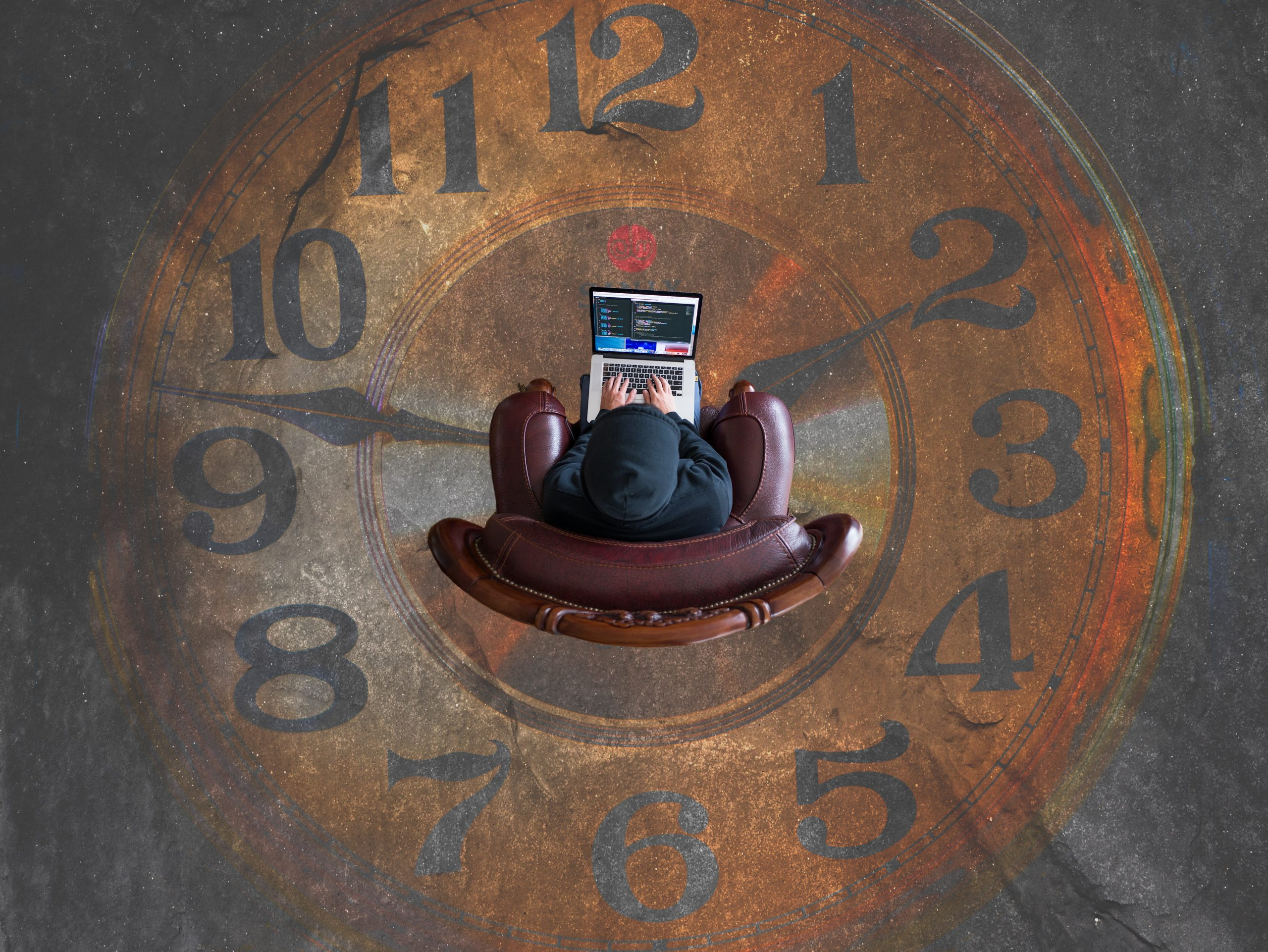 a person sitting at a laptop on a chair in the middle of an image of an analogue clock